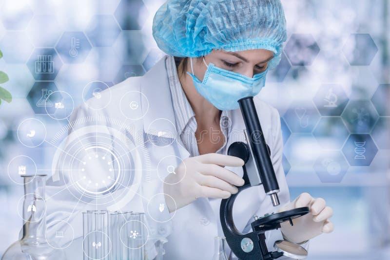 Laborancki asystent egzamininuje niektóre substancję jest przyglądający w mikroskop obraz stock
