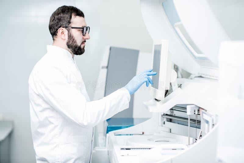 Laborancki asystent pracuje z medyczną analizer maszyną zdjęcie royalty free