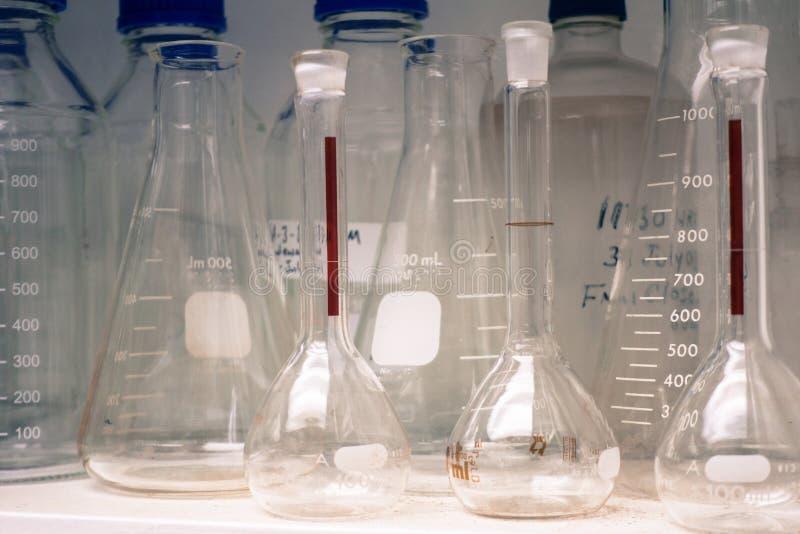 Laborancki glassware lub zlewki w brzmienie stercie na półce zimna i rocznika, nauki badanie, nauki pojęcie zdjęcie stock