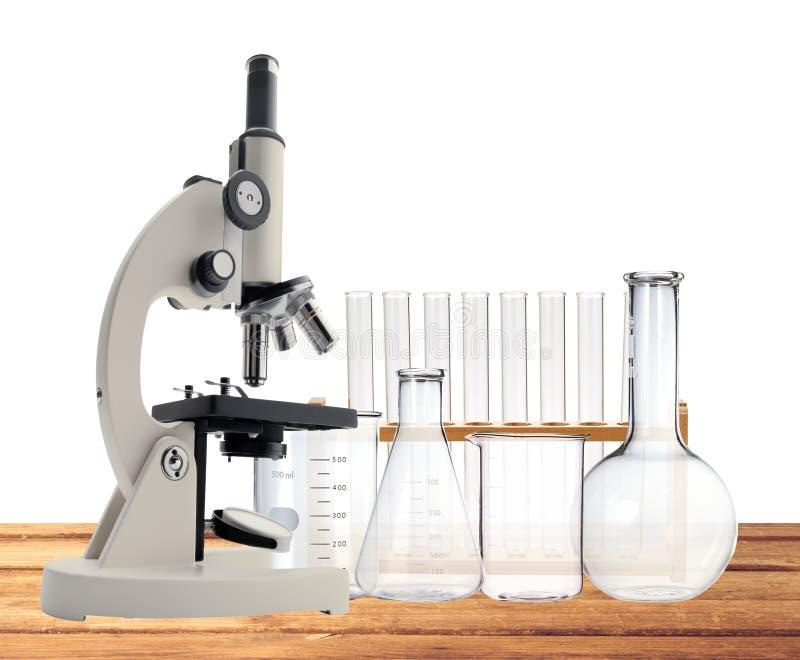 Laborancki metalu mikroskop i próbne tubki na drewnianym stołowym isola fotografia royalty free
