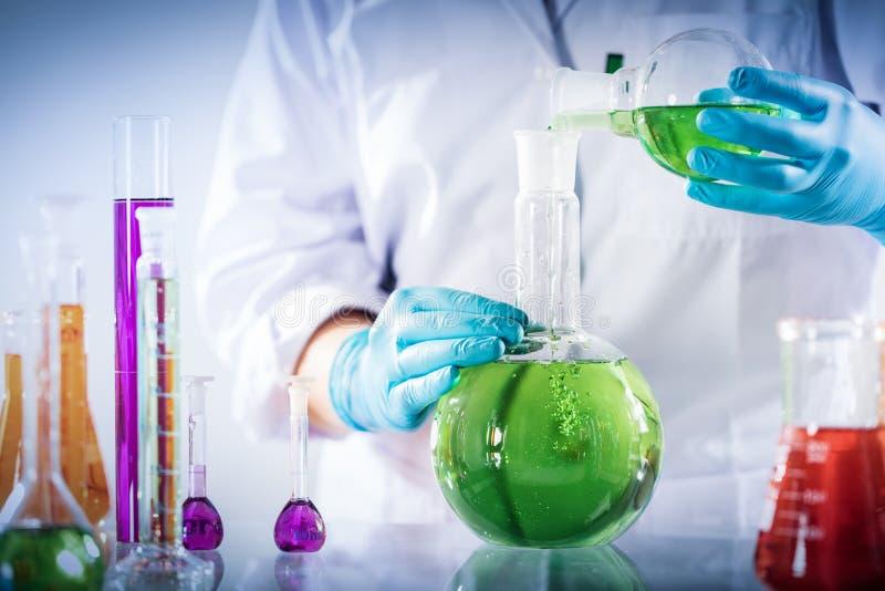 Laborancki pracownik miesza chemiczną ciekłą próbkę fotografia royalty free