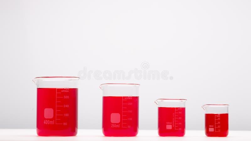 Laborancki wyposażenie, zlewki wypełniał czerwonym cieczem na bielu stole Nauki poj?cie zdjęcie royalty free