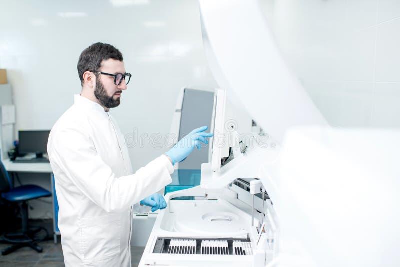 Laborant som arbetar med den medicinska analizermaskinen royaltyfri foto