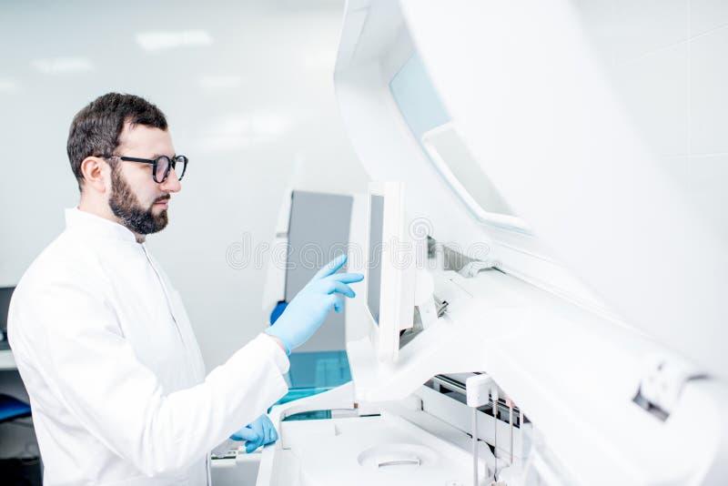 Laborant som arbetar med den medicinska analizermaskinen fotografering för bildbyråer