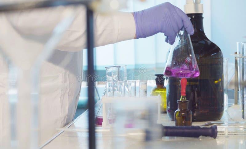 Laboratoire d'analyse chimique Mains d'un scientifique titrant la solution images stock