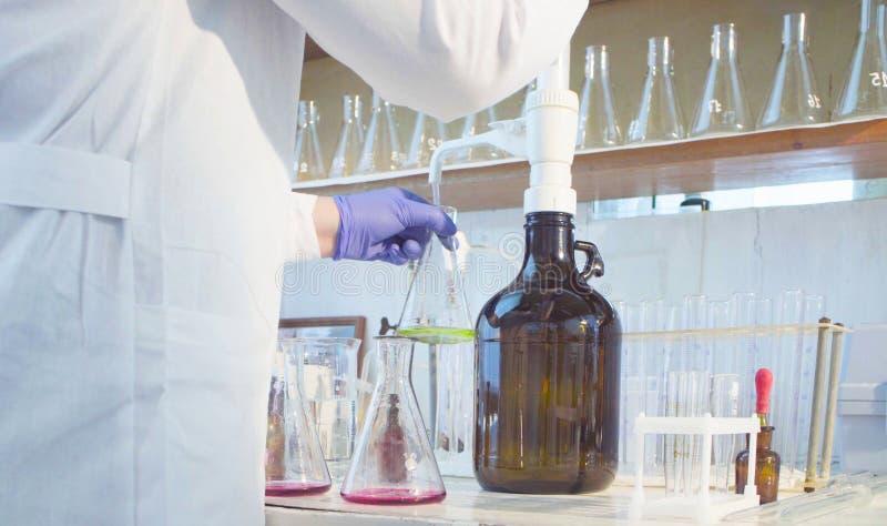 Laboratoire d'analyse chimique Mains d'un scientifique titrant la solution image stock