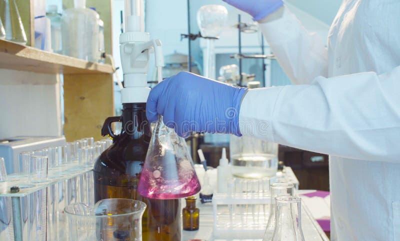 Laboratoire d'analyse chimique Mains d'un scientifique titrant la solution photo stock