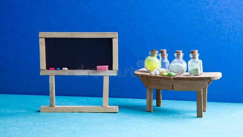Laboratoire de salle de classe de leçon de pharmacie de chimie Tableau vide noir, table en bois et bouteilles en verre de réactif images libres de droits