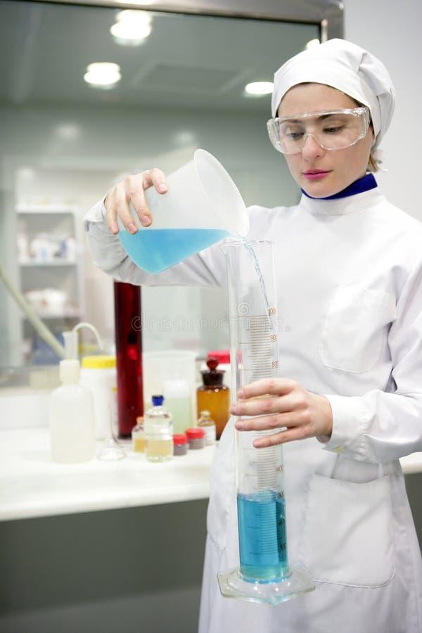 Laboratoire travaillant de femme, vase en verre à cylindre image libre de droits