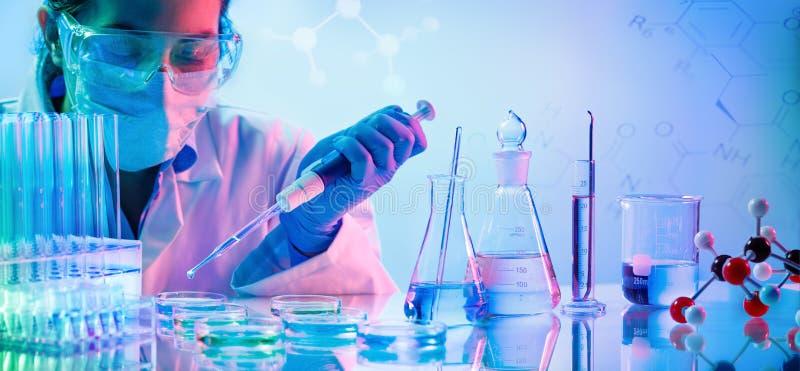 Laboratorio de química - mujer con las pipetas foto de archivo