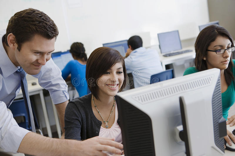 Laboratorio del ordenador de Helping Student In del profesor imagen de archivo