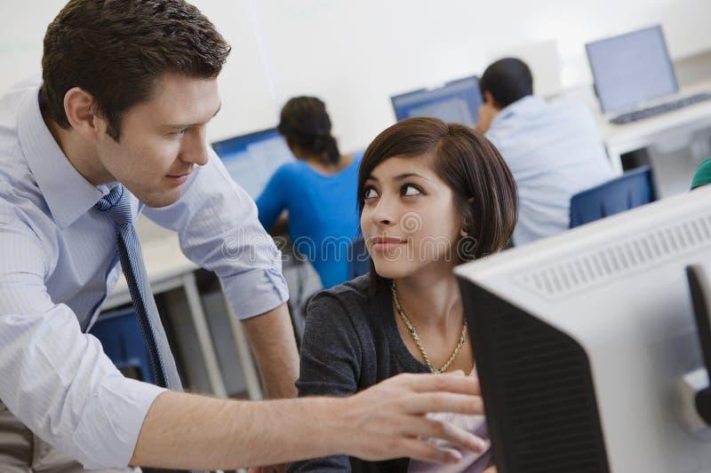 Laboratorio del ordenador de Helping Student In del profesor imagen de archivo libre de regalías
