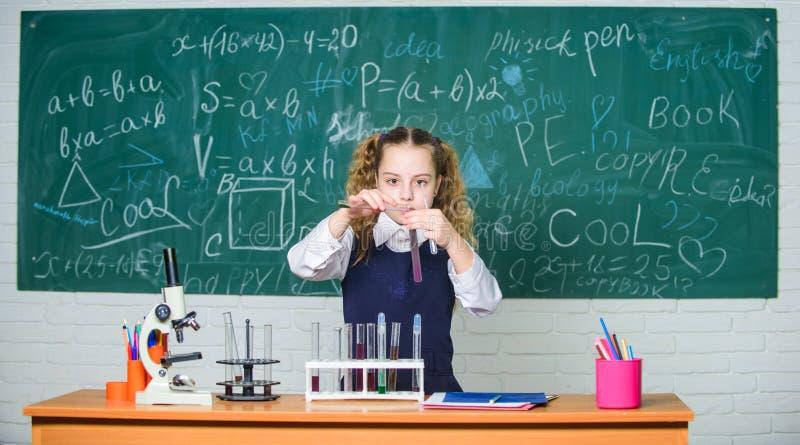 Laboratorio della scuola Esperimento astuto della scuola di comportamento dello studente della ragazza Liquidi chimici di studio  immagine stock