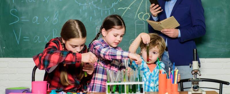 Laboratorio di chimica Di nuovo al banco insegnante felice dei bambini bambini in cappotto del laboratorio che imparano chimica n fotografia stock