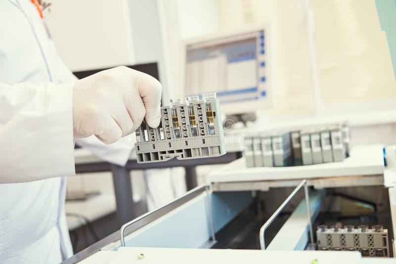 Laboratorio medico biochimico della prova dello stimolante Mano con la prova vicino all'analizzatore immagini stock libere da diritti