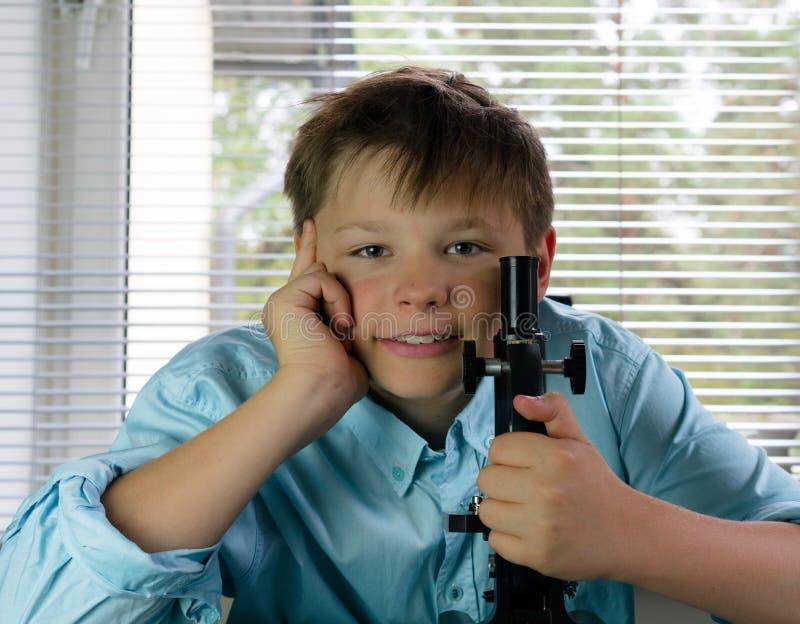 Laboratorio ragazzo e microscopio divertenti Primo piano fotografia stock libera da diritti