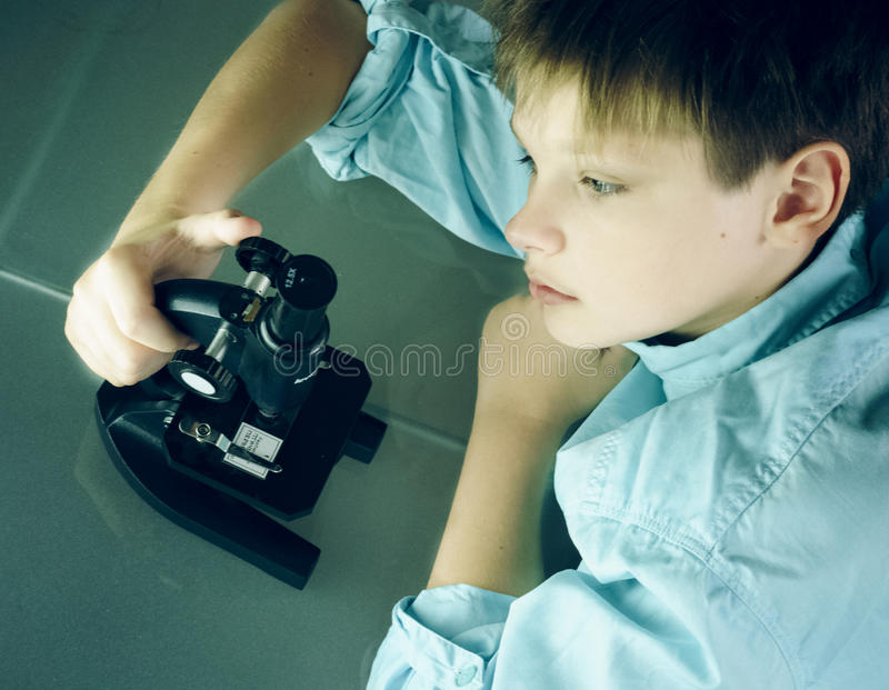 Laboratorio un ragazzo e un microscopio Primo piano Vista superiore immagine stock