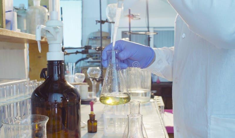 Laboratorium för kemisk analys Händer av en forskare som titrating lösningen royaltyfri bild