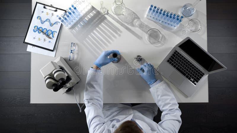 Laboratorium hulp het controleren olieproduct in fles, die chemisch mengsel, hoogste mening maken stock fotografie