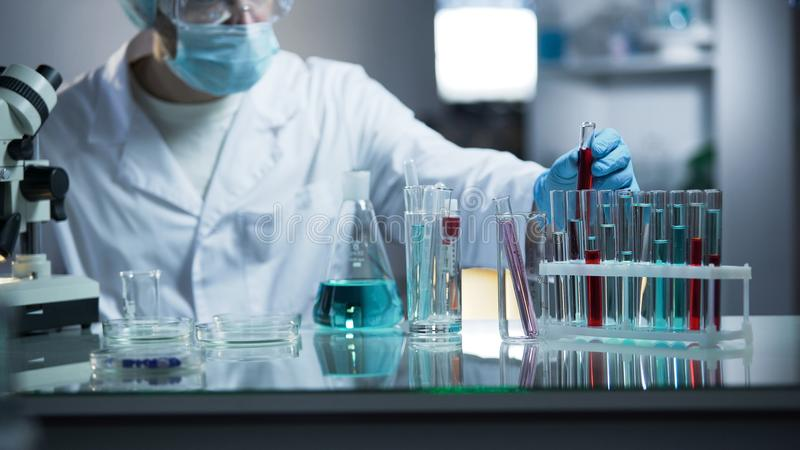 Laboratoriumarbeider die medisch bloedmonster op zijn plaats na het onderzoeken voor sedimenten zetten royalty-vrije stock afbeelding