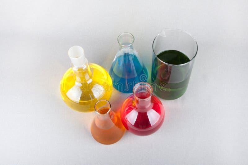 Laboratoriumflaskor med färgflytande på vit bakgrund arkivfoto