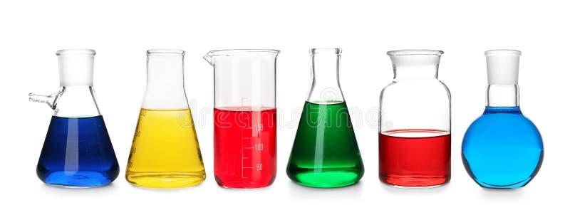 Laboratoriumflaskor med färgprövkopior på vit bakgrund royaltyfri foto