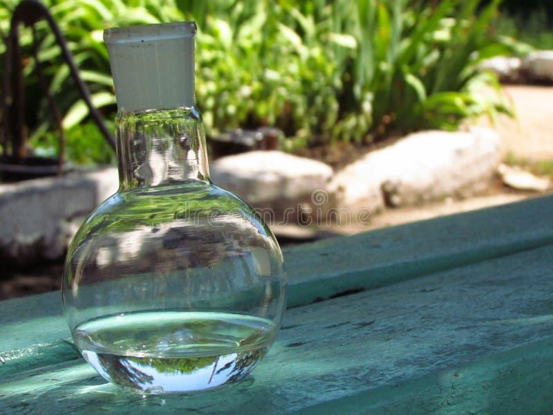 Laboratoriumfles met water op de achtergrond van aard royalty-vrije stock foto's