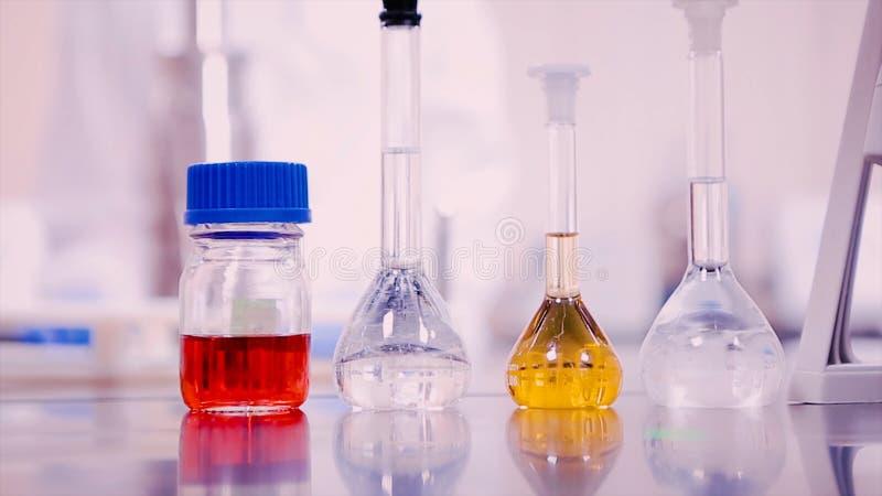 Laboratoriumflessen en bekers met vloeistoffen van verschillende kleuren op laboratoriumlijst stock fotografie
