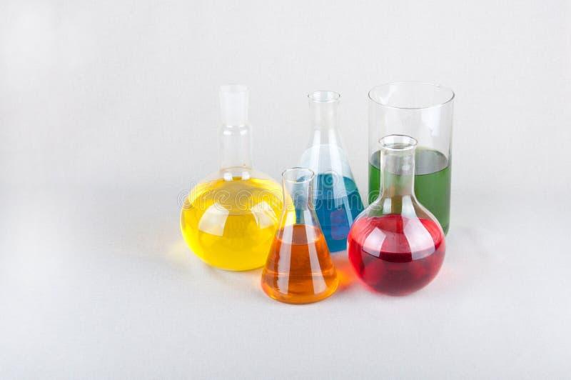 Laboratoriumglasföremål med färgflytande på tabellen royaltyfri fotografi