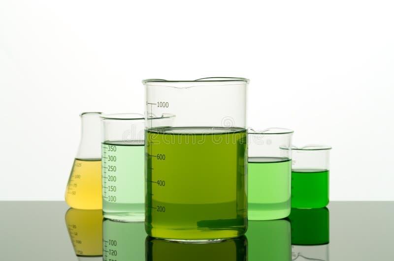 Laboratoriumglaswerk met kleurrijke vloeistof op de lijst stock afbeeldingen