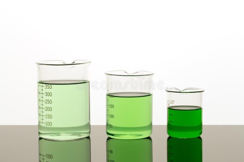Laboratoriummateriaal Drie bekers van verschillende grootte met groene vloeistof royalty-vrije stock foto's