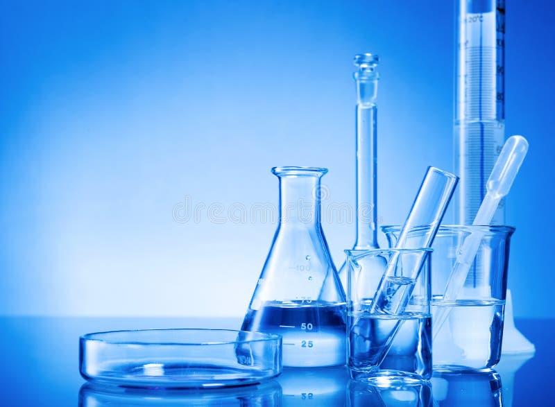 Laboratoriummateriaal, glasflessen, pipetten op blauwe achtergrond stock foto