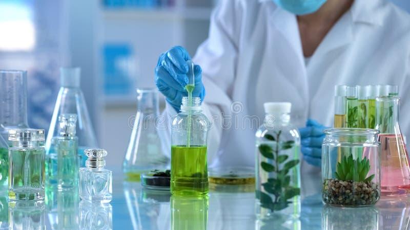 Laboratoriumspecialist die vloeistof met pipet voor het testen, de ontwikkeling van ecoparfums nemen royalty-vrije stock foto