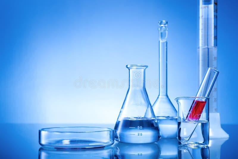 Laboratoriumutrustning, glass flaskor, pipetter, röd flytande arkivfoto