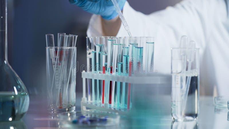 Laboratoriumwetenschapper die tests uitvoeren door daling van reagens aan mengsel toe te voegen stock fotografie