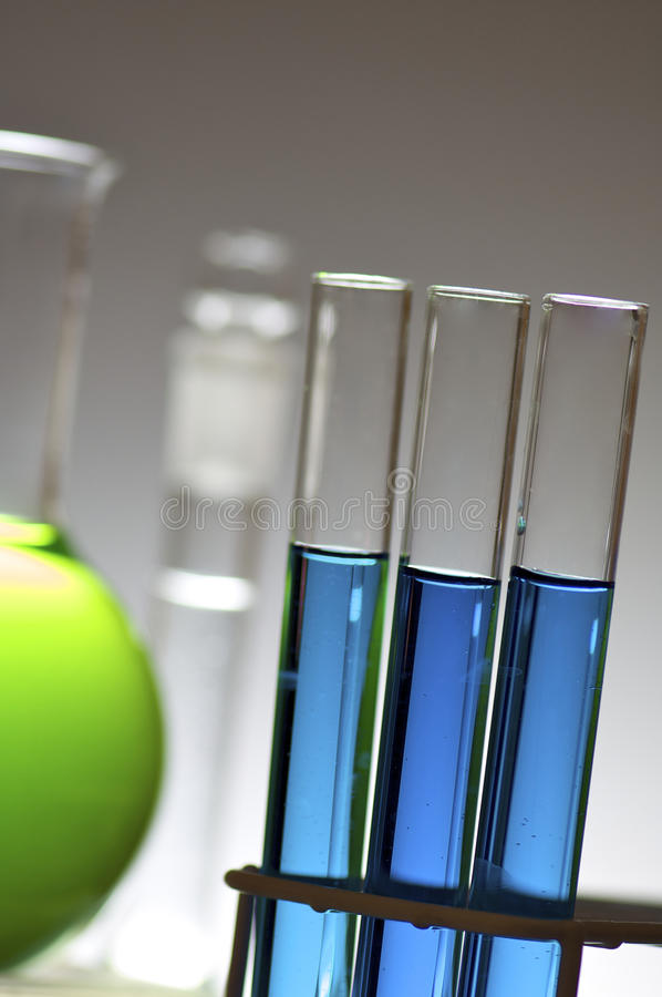 Laboratory. Blue test tubes and bottles with white background royalty free stock photography