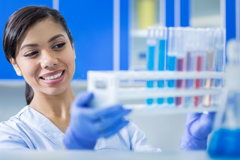 Happy delighted woman holding test tube rack royalty free stock photos