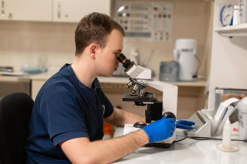 Laboratory assistant looking through microscope. Make research in laboratory. Science and medicine concept.  royalty free stock images