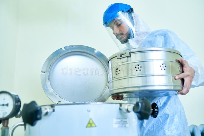 Laboratory assistant putting container into centrifuge royalty free stock images