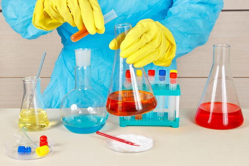 Laboratory assistant in rubber gloves doing chemical analysis in laboratory stock photo