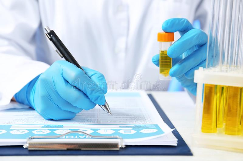 Laboratory assistant with urine sample for analysis writing medical report at table. Closeup royalty free stock photography
