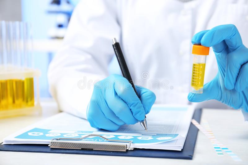 Laboratory assistant with urine sample for analysis writing medical report at table. Closeup royalty free stock photo