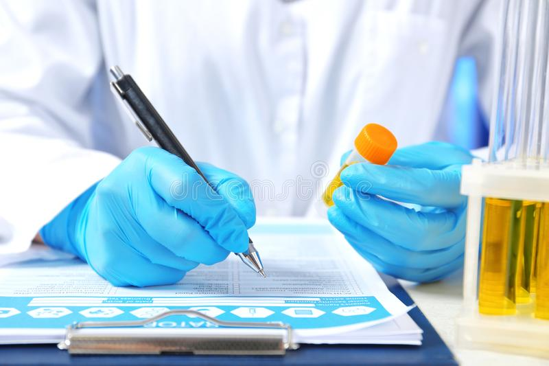 Laboratory assistant with urine sample for analysis writing medical report at table. Closeup stock photography