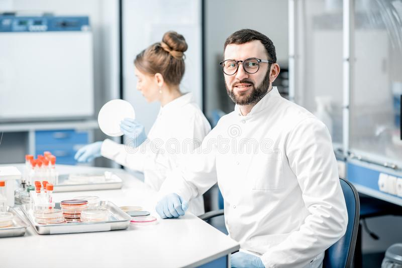 Laboratory assistants in the bacteriological department. Portrait of a men in medical uniform during the bacteriological tests sitting with assistant in the stock photos