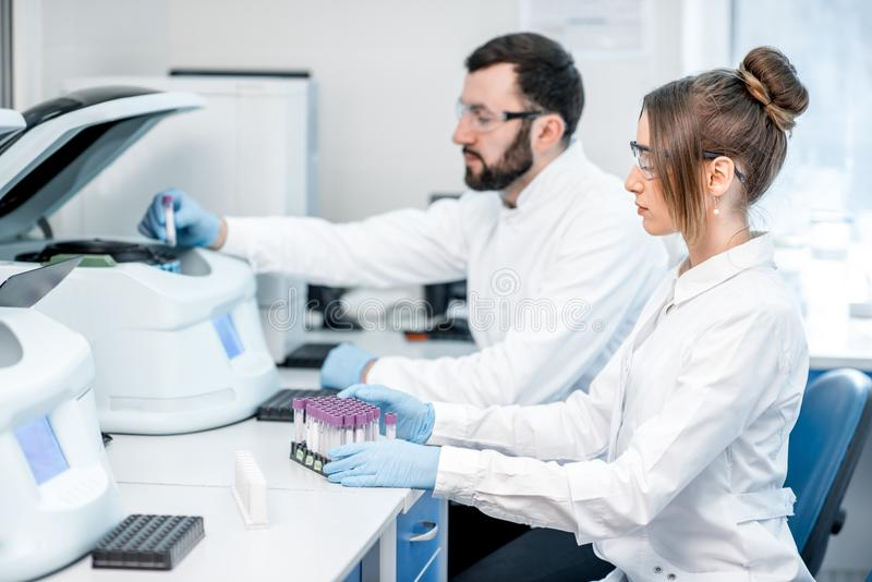 Laboratory assistants making analysis. With test tubes and analyzer machines sitting at the modern laboratory royalty free stock photos