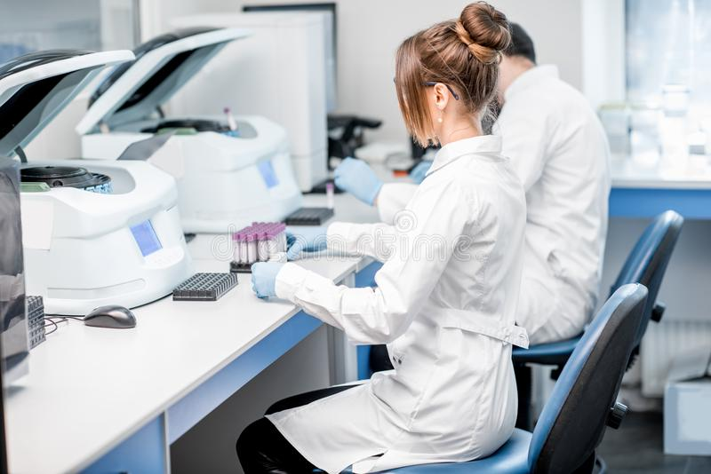 Laboratory assistants making analysis. With test tubes and analyzer machines sitting at the modern laboratory stock photos