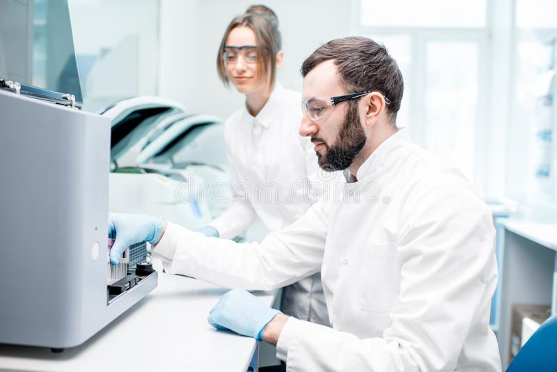 Laboratory assistants making analysis. With test tubes and analyzer machines sitting at the modern laboratory royalty free stock photography