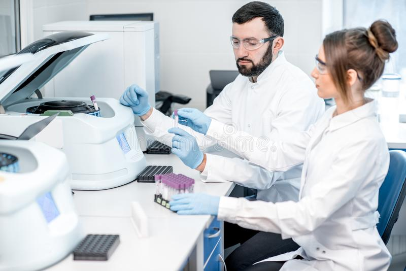 Laboratory assistants making analysis. With test tubes and analyzer machines sitting at the modern laboratory royalty free stock image