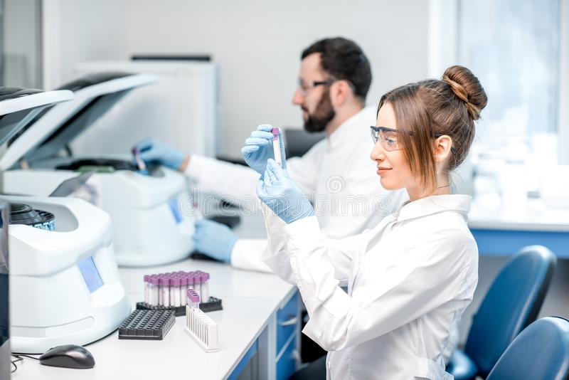 Laboratory assistants making analysis. With test tubes and analyzer machines sitting at the modern laboratory royalty free stock photo