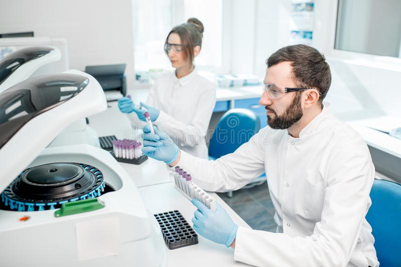 Laboratory assistants making analysis. With test tubes and analyzer machines sitting at the modern laboratory stock photography